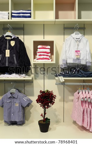 children clothing store, clothing on shelves, hangers with jackets, artificial tree - stock photo