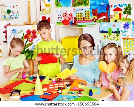 Children  cutting out scissors paper in preschool. - stock photo