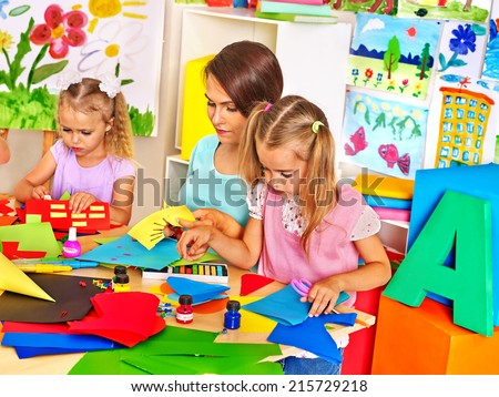 Children  cutting out scissors paper in preschool.