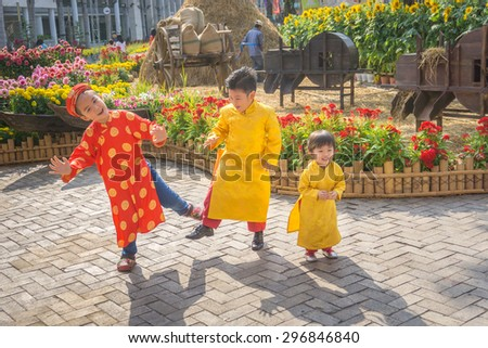 "Children dancing happy laughing/HoChiMinh, Vietnam â?? February 13th 2015: The three kids wear ""Ao dai"". ""Ao dai"" is traditional clothes of Viet Nam. They dance to welcome a New Year"