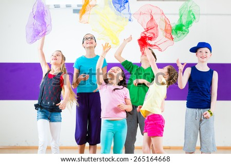 Children dancing modern group choreography with scarfs - stock photo