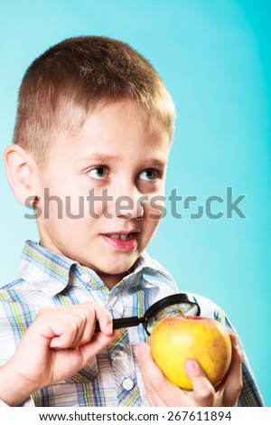 Children development. Child examining apple looking through a magnifying glass. Environmental awareness education. - stock photo