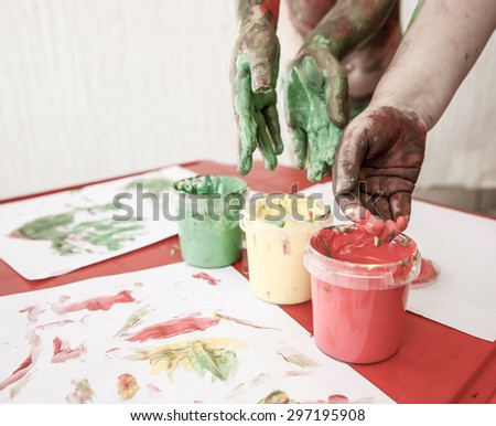Children dipping fingers in washable, non-toxic finger paints, painting a drawing. Sensory play, permissive parenting, fun childhood concept, desaturated. - stock photo
