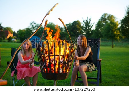 children doing campfire bread over fire - stock photo