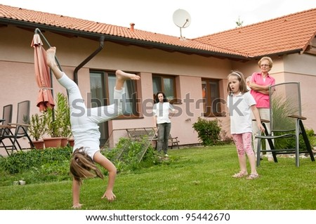Children doing cartwheels in backyard - stock photo