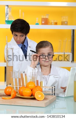 Children doing chemistry experiments with orange juice - stock photo