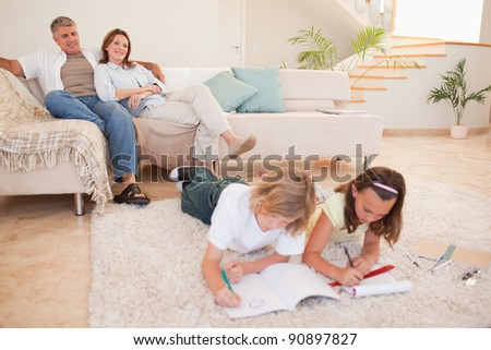 Children doing homework with their parents behind them - stock photo