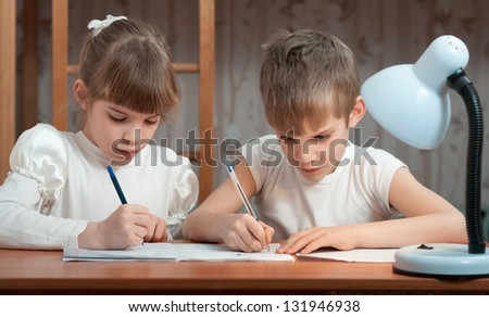 children draw in a notebook at the table