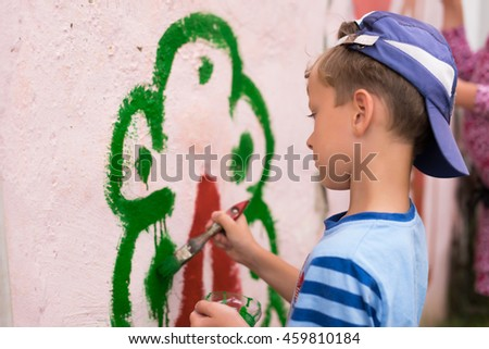 Children drawing on the wall depict the house in the summer outdoors