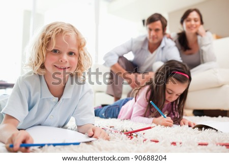 Children drawing while their parents are in the background in a living room - stock photo