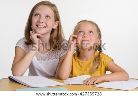 Children during preparation for their lessons in school. Two cuties think over about their subjects and smile while looking upwards. - stock photo