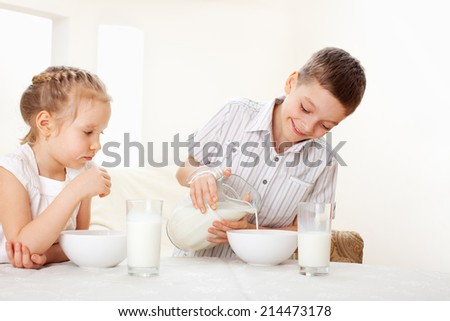 Children eat breakfast. Family eating cereals with milk - stock photo