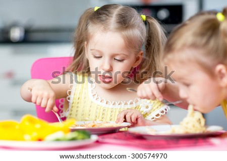 Children eat spaghetti with vegetables in nursery - stock photo