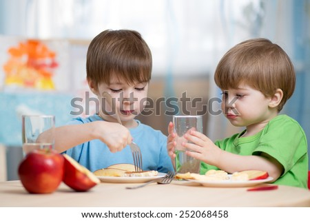 children eating  and drinking at home or kindergarten - stock photo