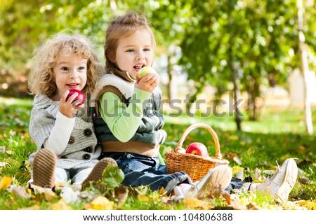 Children eating apples in autumn park. Family picnic - stock photo