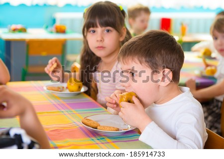 Children eating baked apple and cookie at kindergarten
