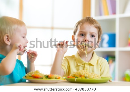 Children eating healthy food in home or daycare center