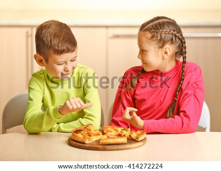 Children eating pizza at home - stock photo