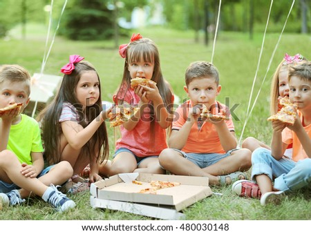 Children eating pizza on grass