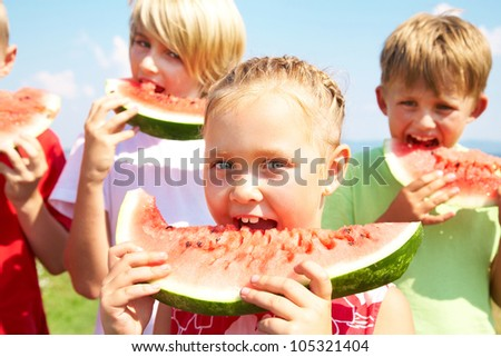 Children eating red watermelon on blue sky background - stock photo