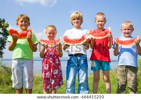 Children eating red watermelon on blue sky background