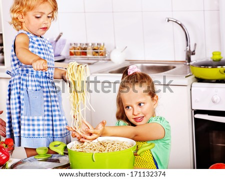 Children  eating spaghetti at kitchen. - stock photo