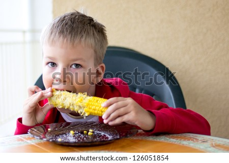 Children eats corn
