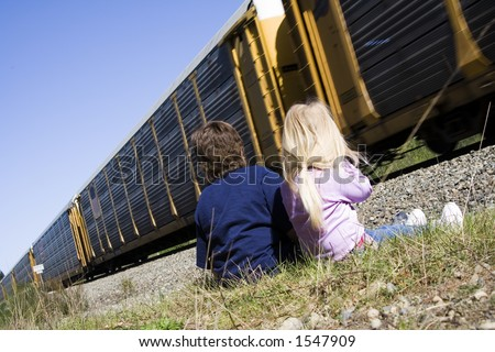 Children enjoy a passing train on a warm sunny afternoon.