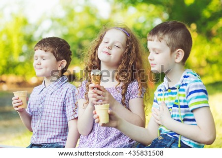 Children enjoy eating ice cream in summer park. - stock photo