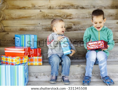children enjoy gifts. Two cute brothers are happy with gifts - stock photo