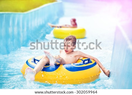 Children enjoying summer vacation in aquapark riding on slide with yellow floats - stock photo