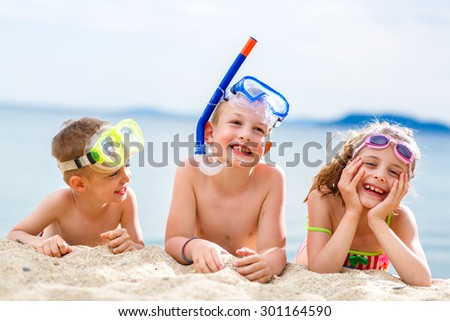 Children enjoying their time on the beach with scuba gear. - stock photo
