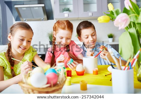 Children enthusiastic about painting eggs - stock photo