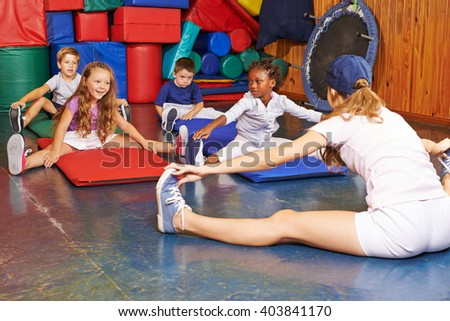 Children exercising in physical education with sports teacher - stock photo