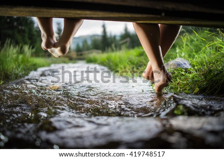 Children feet playing and having fun time on the beautiful mountain creek