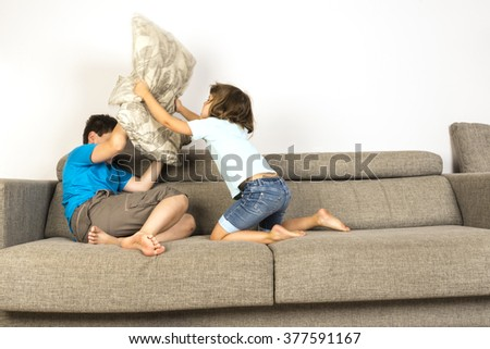 Children fighting together with pillows on sofa at home