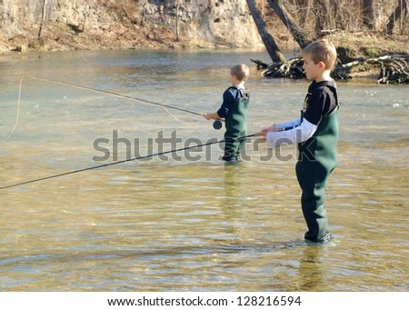 Children fishing - brothers and friends learning to fly fish in a clear stream - stock photo