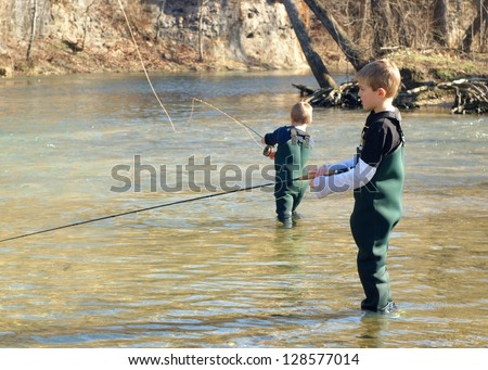 Children fishing - brothers and friends learning to fly fish in a clear stream (focus centered on boy in front) - stock photo