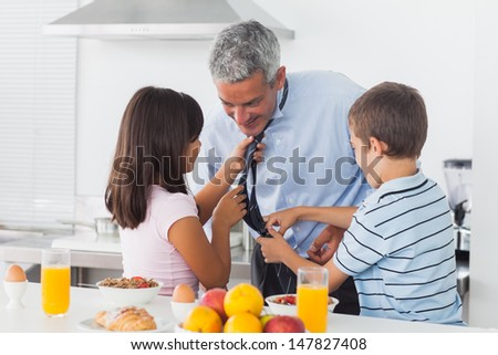 Children fixing their fathers tie in the kitchen at home - stock photo