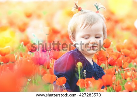 Children - flowers of life. Funny child holding a flower at outdoor at poppy field. Baby girl. Summer. Children's Day celebrating on first June, 1 or 14 November