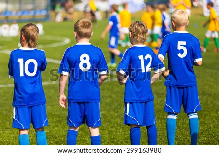 Children football soccer match. Team waiting on a bench. Ready to play soccer game - stock photo