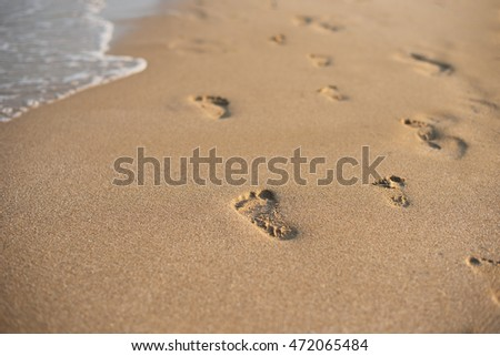 Children footprints in the sand. Human footprints leading away from the viewer. A row of footprints in the sand on a beach in the summertime. Summer Vacation