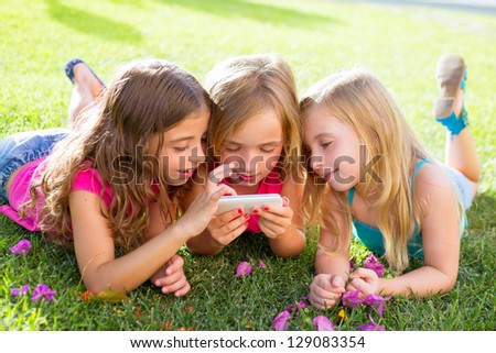 children friend girls group playing internet with mobile smartphone on grass - stock photo