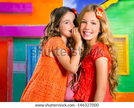 children friends girls whispering ear in vacation at tropical colorful house - stock photo