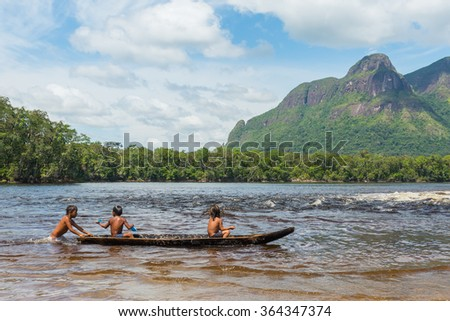 Children from the Piaroa ethnicity play on a canoe in the waters of the Autana river, in the amazonas state, in southern Venezuela  - stock photo