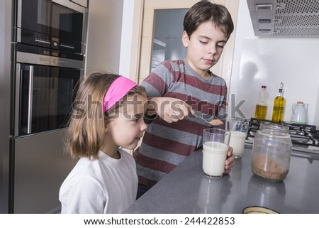 Children getting ready a glass of chocolate milk