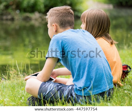 Children - girl and boy, with tablet pc at lakeside. Family - brother and sister, have rest near water in park. - stock photo