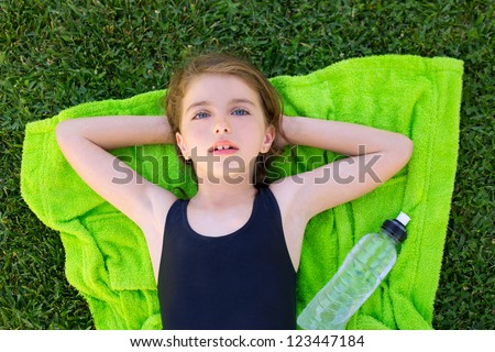 children girl relaxed lying on towel over green grass with water bottle in swimsuit - stock photo
