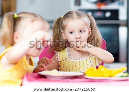 Children girls eating healthy food in kindergarten or at home - stock photo