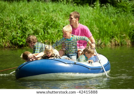 Children go for a drive on an inflatable boat under supervision of adults - stock photo